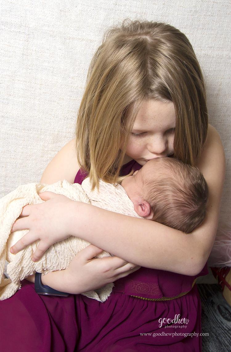 Newborn Photography - Big sister kissing newborn baby